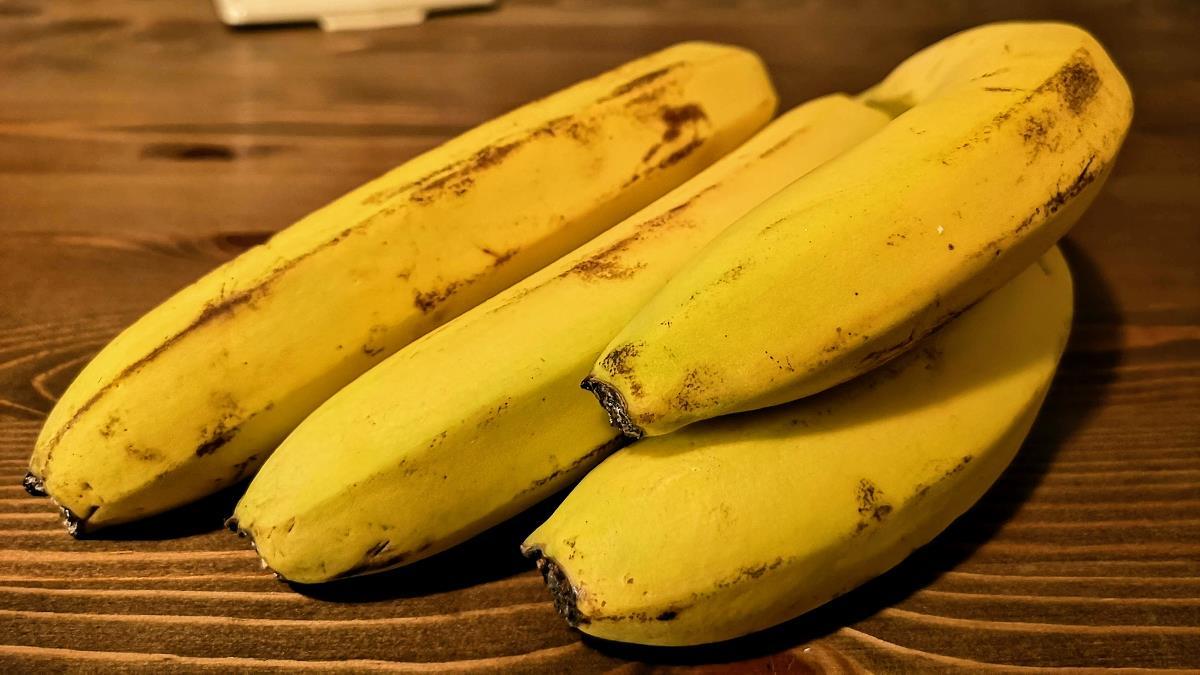 Vier gelbe Bananen auf einem Holztisch